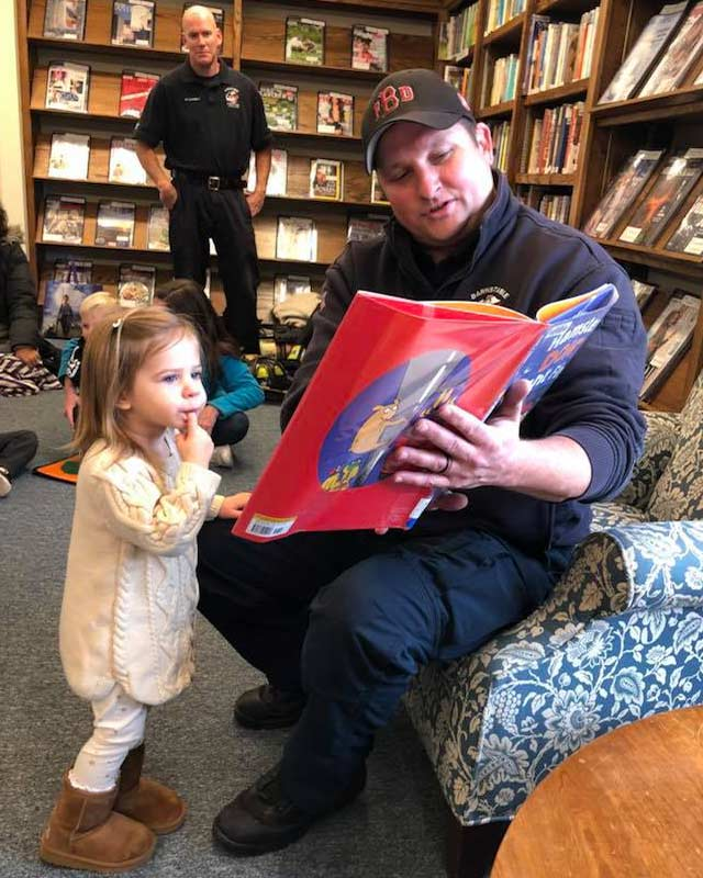 a father reading to his daughter in the library