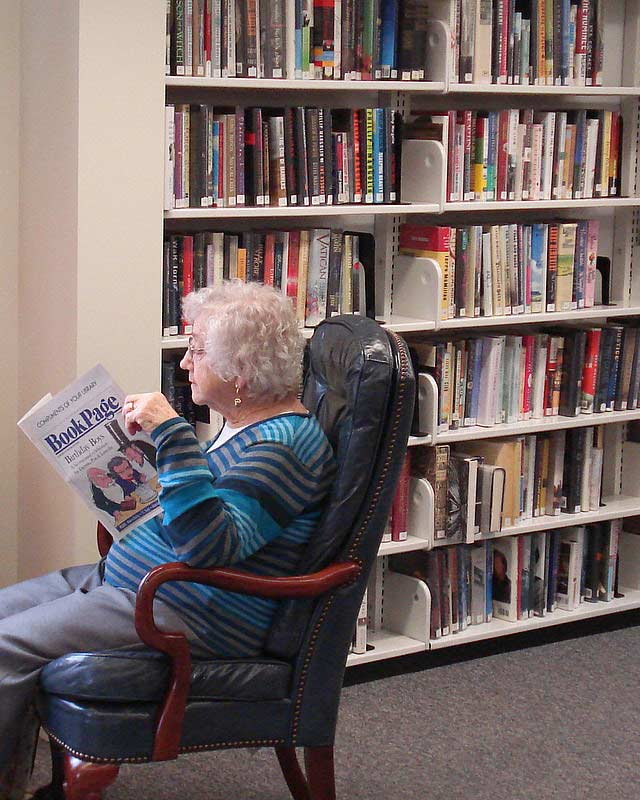 older woman reading and enjoying a book